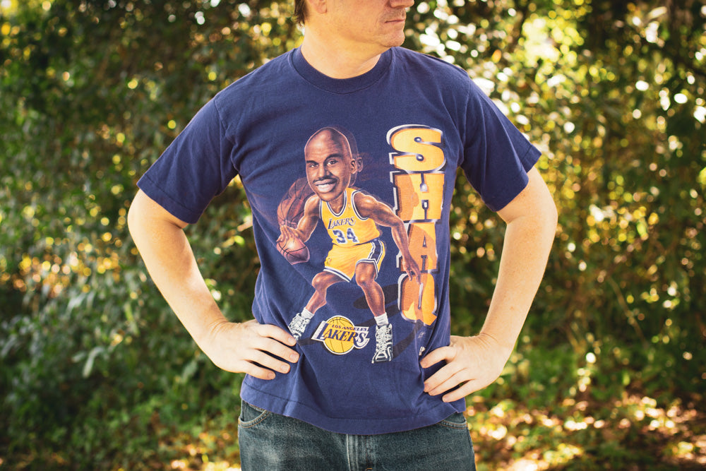 Man wearing a vintage Shaquille O'Neal Los Angeles Lakers t-shirt outside.