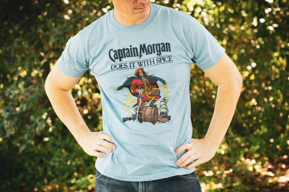 Man wearing a vintage Captain Morgan Rum t-shirt outside.