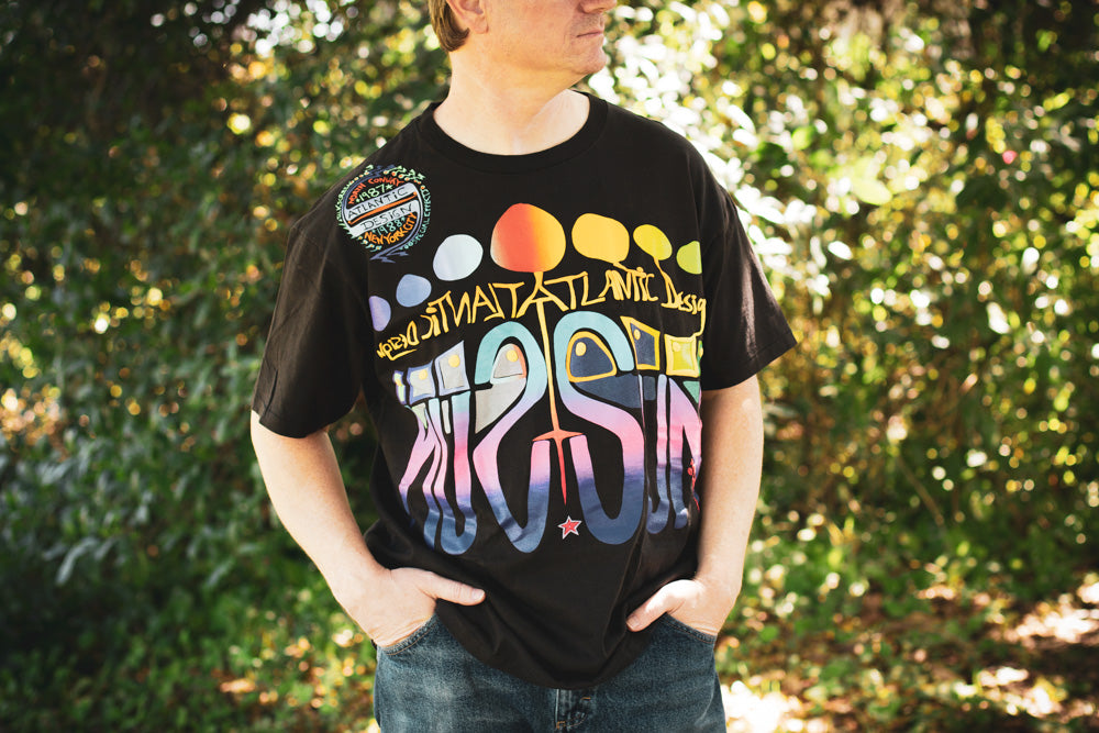 Man wearing a black vintage 80s t-shirt with multicolored graphics advertising Atlantic Sun Design