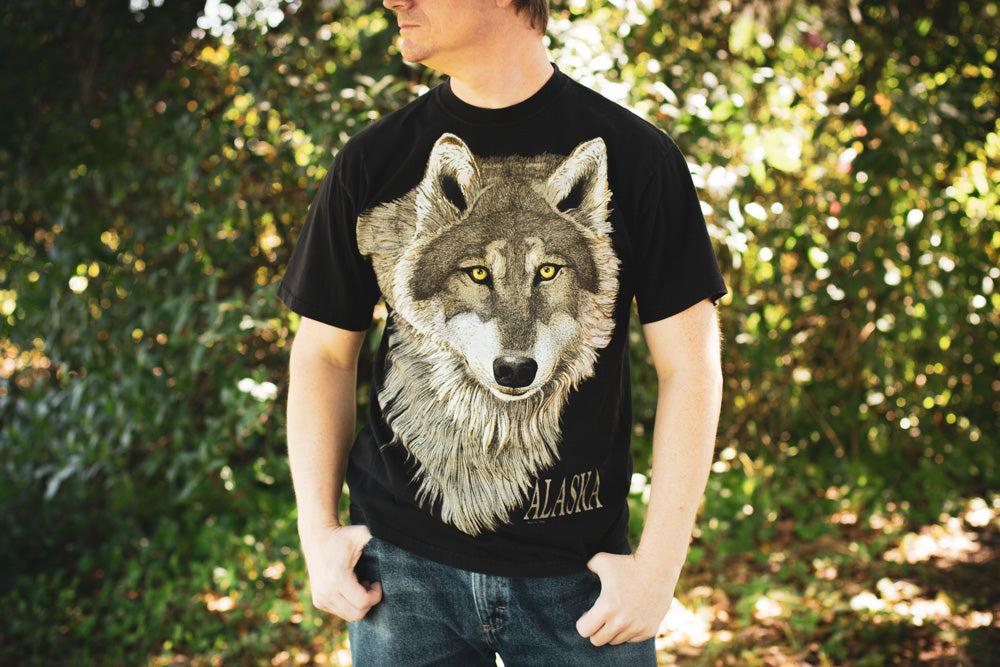 Man wearing a vintage 90s black t-shirt with a large graphics of a wolf's head