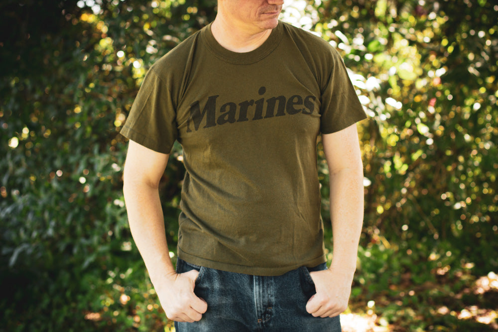 Man wearing a green vintage 80s t-shirt with text reading Marines