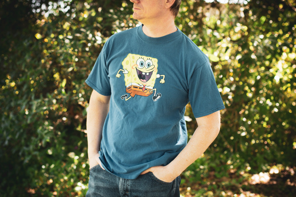 Man wearing a blue vintage t-shirt with graphic of SpongeBob SquarePants smiling and running