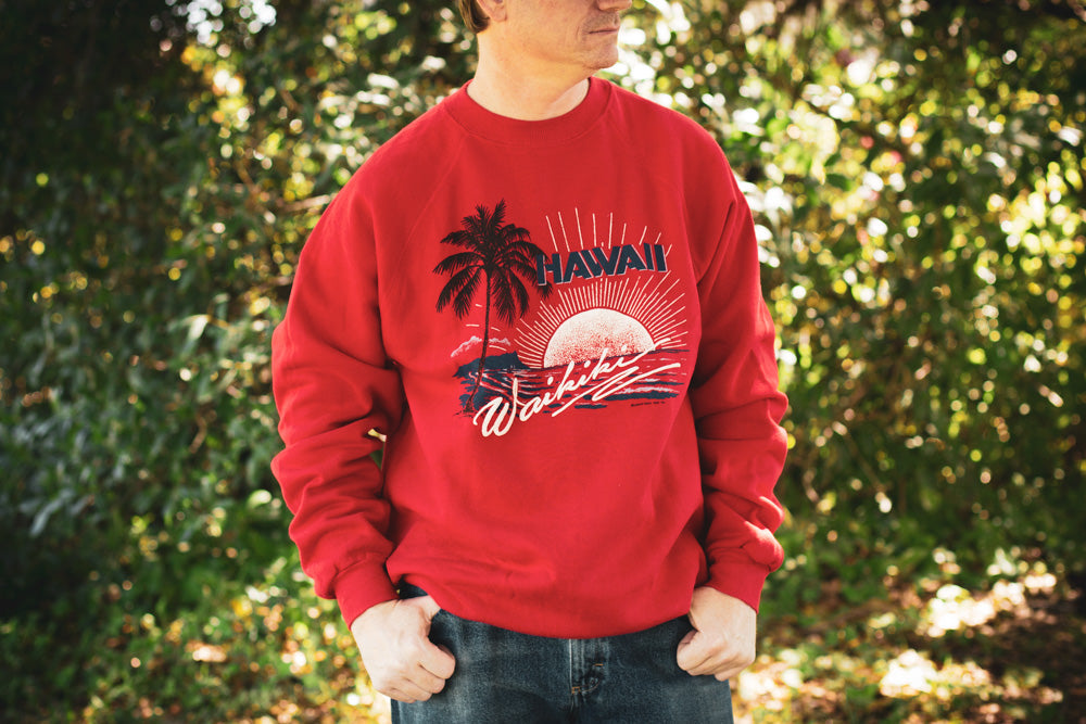 Man wearing a red vintage 80s sweatshirt with tropical graphics and Waikiki text