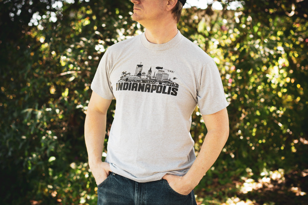 Man wearing a grey vintage 80s t-shirt with Indianapolis cityscape and text