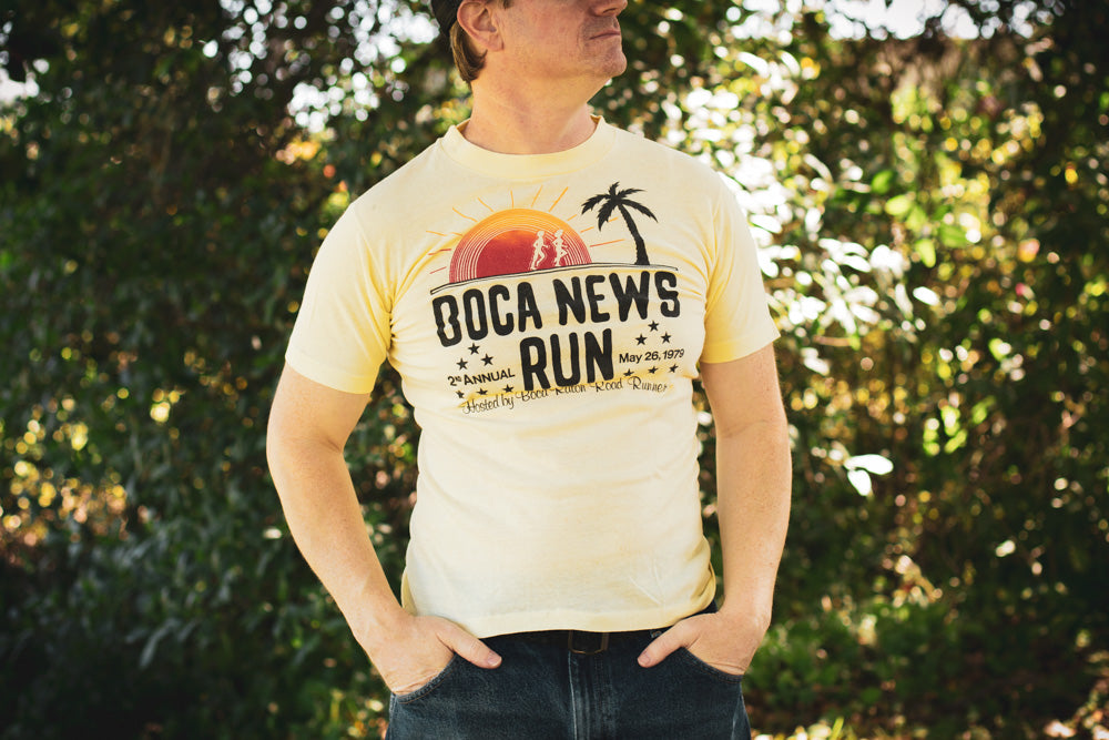 Man wearing a vintage light yellow t-shirt with tropical graphics and text from the 1979 Boca News Run