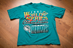 Teal t-shirt with logo and text celebrating the Florida Marlins as 1997 World Series Champions