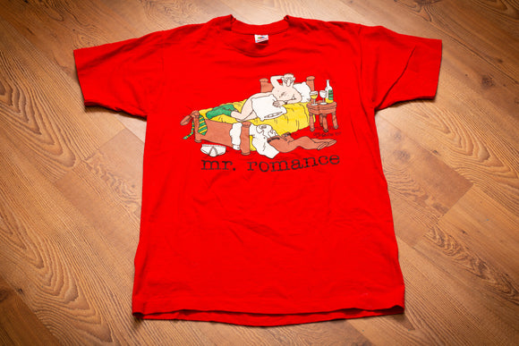 Vintage 80s red t-shirt with drawing by Jim Benton of a middle-aged man smiling naked on the bed with pillow over private area and