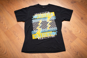 black t-shirt with jonezetta band text and yellow, blue and white 80s-style graphics