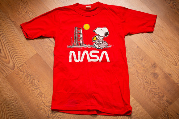 vintage 80s kids red t-shirt with nasa logo and snoopy as an astronaut walking towards a space shuttle