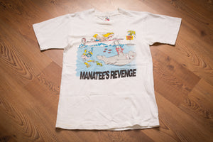 vintage 90s white t-shirt with cartoon graphic of a manatee taking a chainsaw to the bottom of a speeding boat
