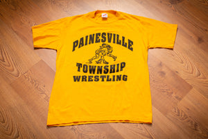 vintage 80s yellow t-shirt with graphic of two boys wrestling and painesville township wrestling text