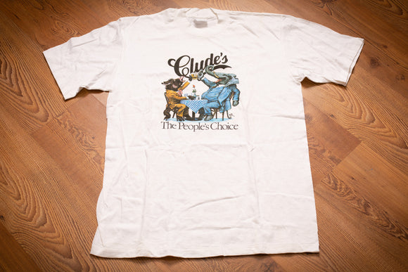 Vintage 80s white t-shirt from Clyde's Restaurant with iconic political graphic of donkey and elephant toasting drinks at a table and laughing