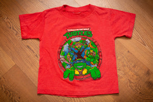 vintage 80s red t-shirt with graphic of teenage mutant ninja turtles looking into a sewer