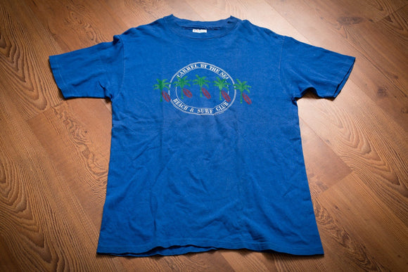 vintage 80s to 90s blue t-shirt with palm tree graphics and text for carmel by the sea beach and surf club in california