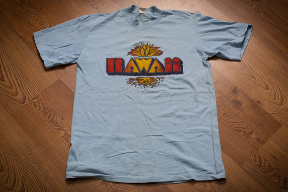 vintage 80s light blue t-shirt with retro hawaii text and sunset graphics