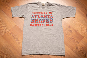 vintage 80s gray t-shirt with red text reading property of atlanta braves baseball club