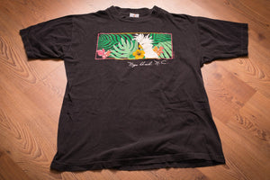 Black t-shirt from Nags Head, North Carolina with graphic of cockatoo amidst green foliage