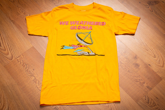 vintage 80s yellow t-shirt with we weathered gloria text and graphic of a man being blown by hurricane winds while holding onto a satellite dish on a building