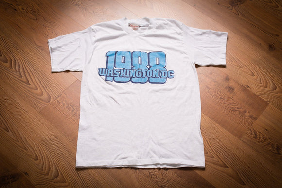 White t-shirt with blue text that reads