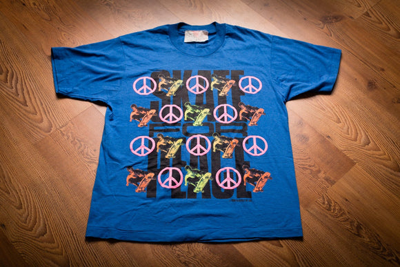 Vintage 1980s blue t-shirt with skateboarding and peace sign graphics and the text