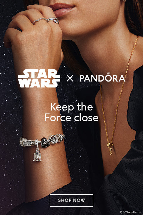 star wars x pandora model wearing R2-D2, Darth Vader, and C3-P0 charms on a bracelet and shine necklace, with her hand by her chin thinking about the baby yoda charm and stacking the wish rings.