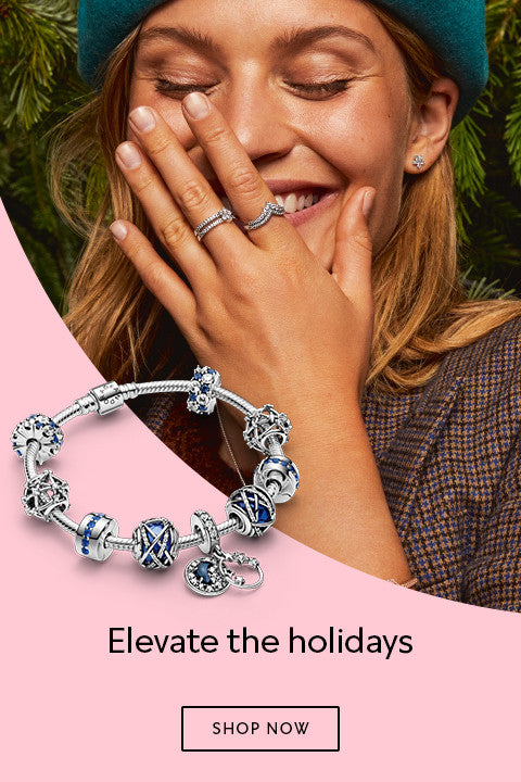 Pandora Jewelry Elevate the Holidays Banner Image featuring blue celestial charm bracelet and Model giggling in front of Christmas Tree and wearing Pandora Rose Charm Bracelet and sterling silver rings.