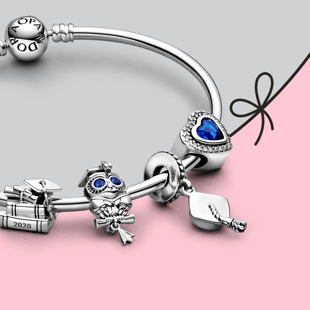 Close up of silver bangle bracelet with graduation themed charms (stack of books, Owl with blue zirconia eyes wearing cap and holding diploma, graduation cap, and blue cz heart charm