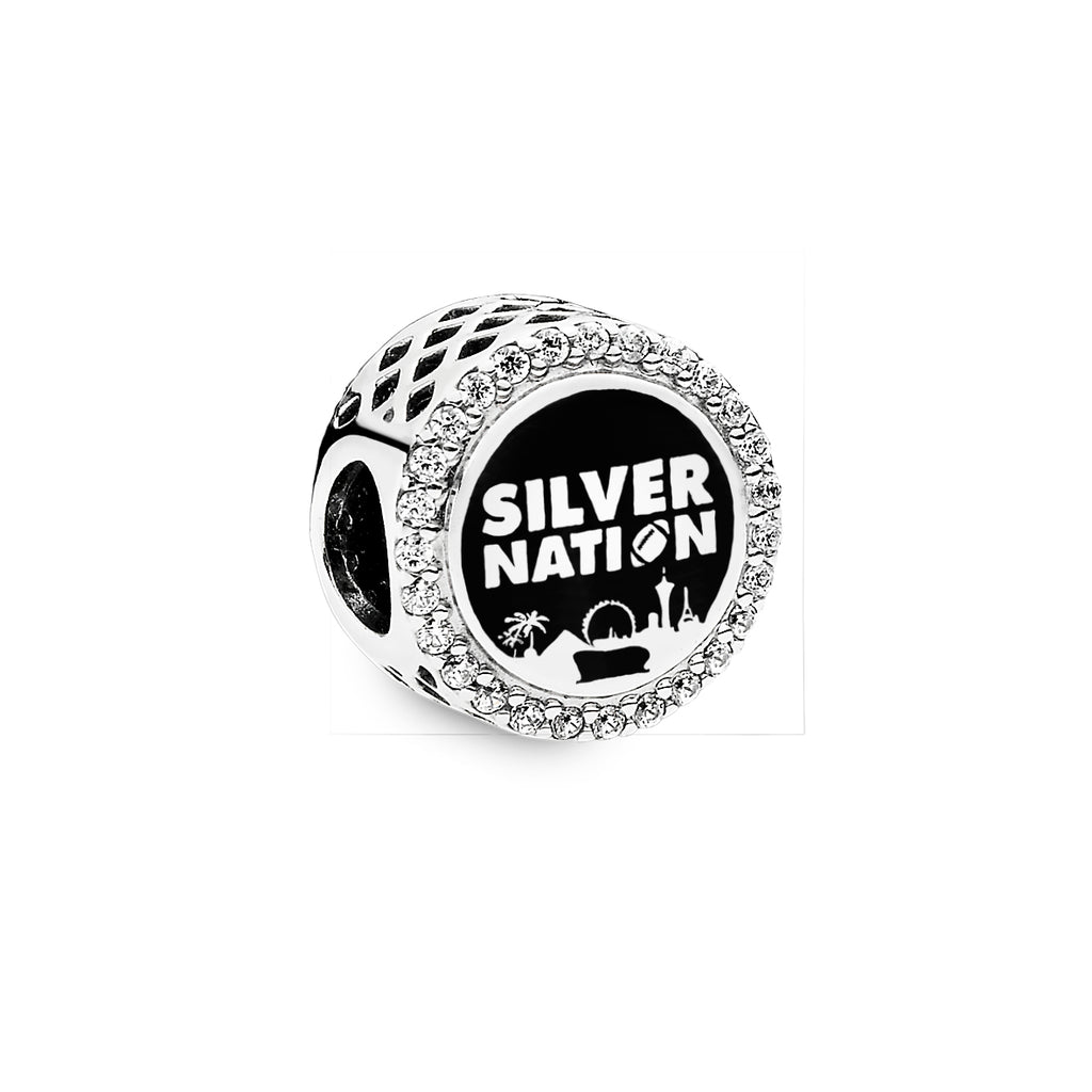 "Pandora Las Vegas exclusive charm in sterling silver with black enamel and cubic Zirconias.  Button shaped charm features the Vegas skyline in silver with the Raiders stadium in the foreground in black  enamel above the skyline ""SILVER NATION"" with an O for the football is in silver with the black enamel sky surrounding it."