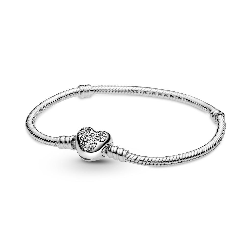 Disney Pandora Moments Mickey Mouse Heart Clasp Snake Chain Bracelet in sterling silver. The clasp is heart-shaped with Mickey Mouse's silhouette on the front decorated with clear stones and outline on the back.