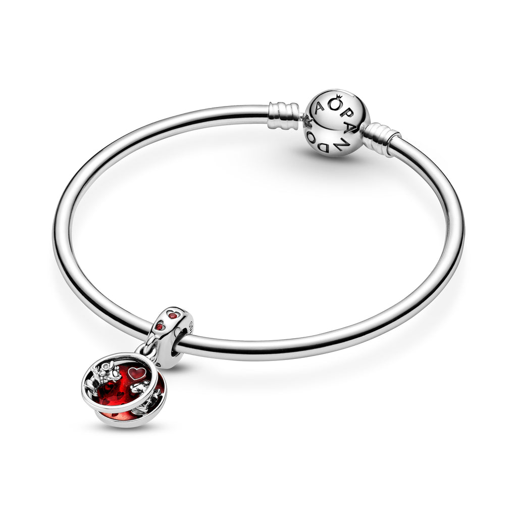 "Pandora Disney Mickey Mouse & Minnie Mouse Love and Kisses Dangle Charm in sterling silver featured on a moments bangle bracelet. The open front disc includes Minnie Mouse's silhouette. The back disc features Mickey Mouse in front of the shaded red and magenta transparent enamel with hearts. The backside of the disc is engraved ""Love and Kisses,"" and red stones in heart-shaped settings decorate the bail."