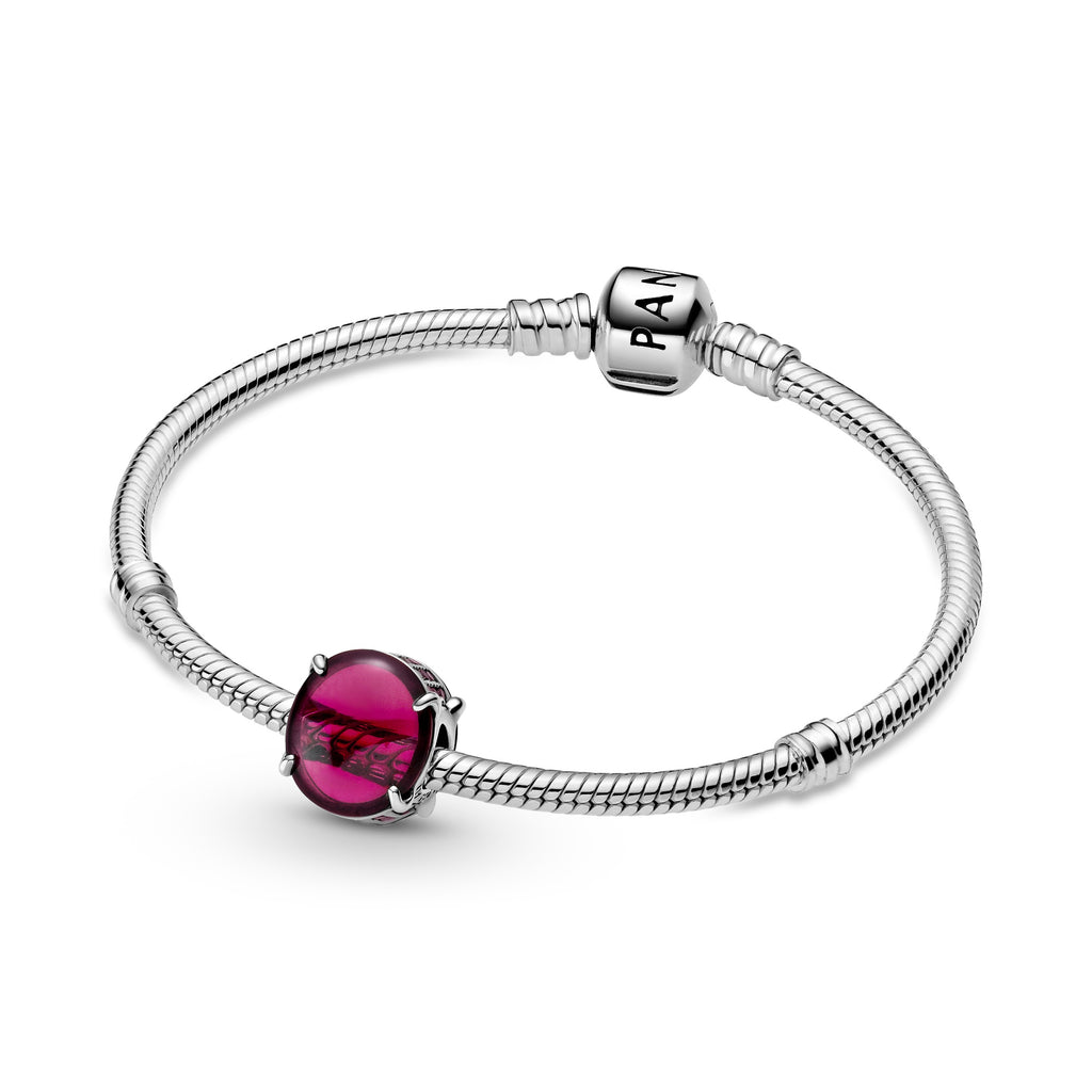 Pandora Fuchsia Rose Oval Cabochon Charm in sterling silver featured on sterling silver bracelet. Two oval cabochon-cut stones create a see-through button-shaped charm. The bottom and top are lined with small sparkling fuchsia stones.
