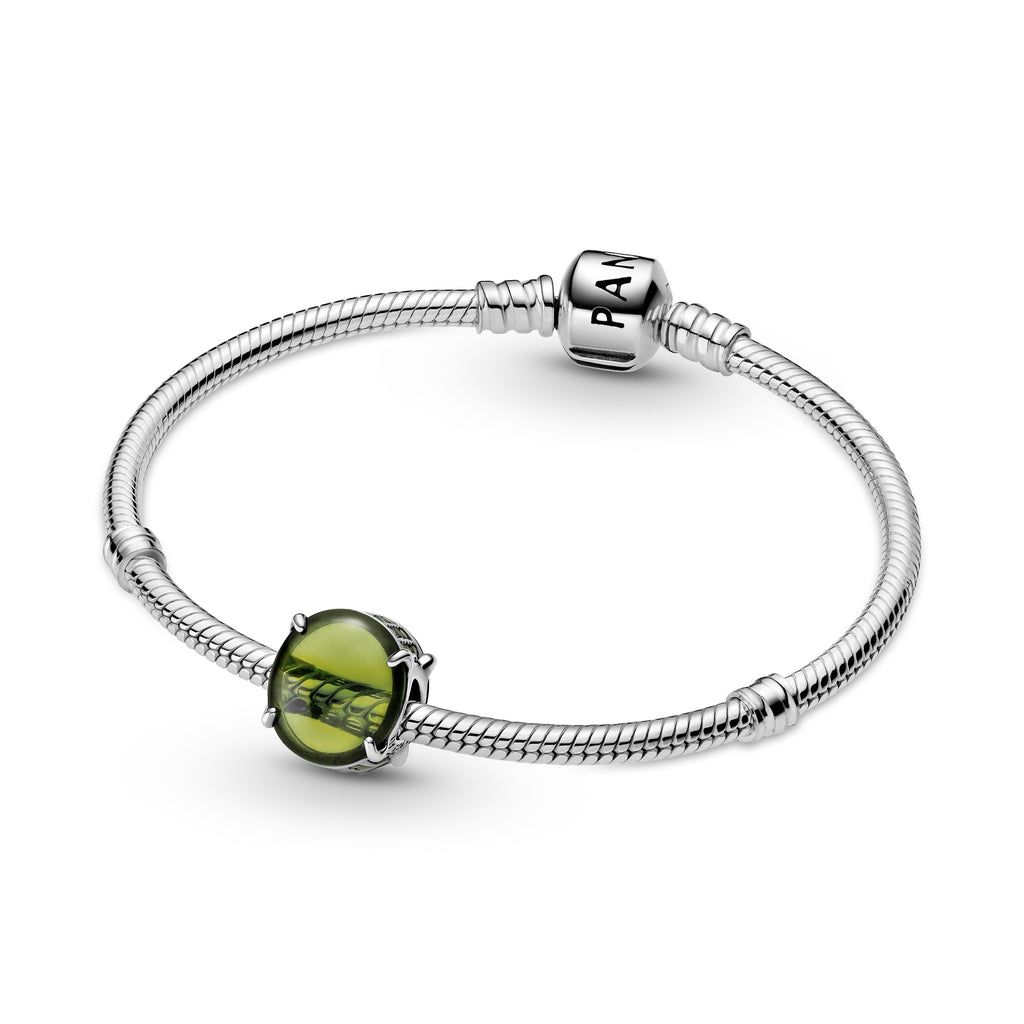 Pandora Green Oval Cabochon Charm featured on Moments Bracelet in sterling silver. Two oval cabochon-cut stones create a see-through button-shaped charm. The bottom and top are lined with small sparkling green stones.