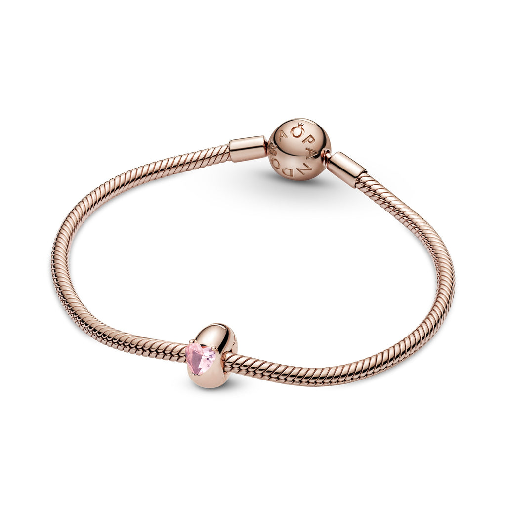 Pink Heart Solitaire Clip Charm in Pandora Rose™ (14k rose gold-plated unique metal blend). This charm is inspired by the look of solitaire rings with a raised heart-shaped stone crystal. This clip charm has a silicone grip inside shown featrued on moments snake chain bracelet.