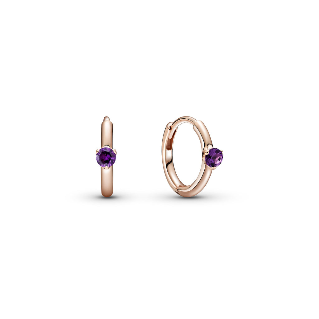 Pandora Purple Solitaire Huggie Hoop Earrings. Hand-finished in Pandora Rose™ (14k rose gold-plated unique metal blend), each hoop features a royal purple stone.