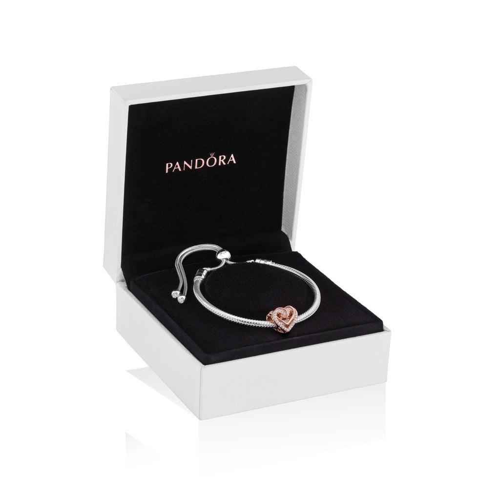 Pandora Sparkling Entwined Hearts Bracelet Gift Set contrasts soft blush hues with brilliant cubic zirconia sparkle. It features the intricately designed Sparkling Entwined Hearts Charm in Pandora Rose on a sleek Pandora Moments Snake Chain Slider Bracelet in sterling silver. Featured in a large Pandora gift box.