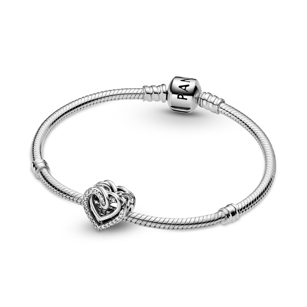 Pandora Sparkling Entwined Hearts Charm. The heart shaped charm has intertwining polished sterling silver hearts and sparkling stone-embellished hearts on the front and back. Entwined hearts are also featured on the sides. Featured on silver moments bracelet.