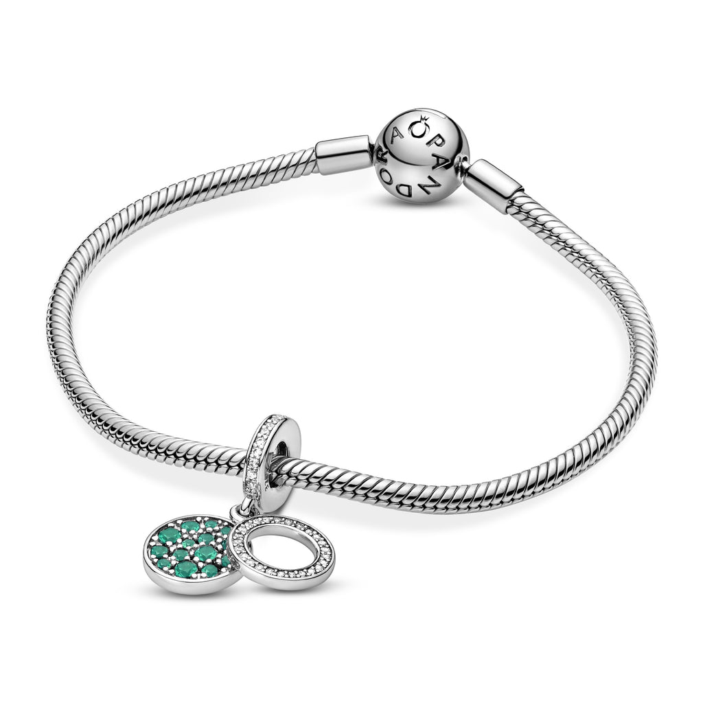 Pandora Sparkling Green Disc Double Dangle Charm in sterling silver. The back disc has beading with green stones in various sizes. The Pandora logo and crown O monogram are on the back. The front open circle disc has clear cubic zirconia.  Featured on Silver moments bracelet.