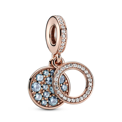 Pandora Sparkling Light Blue Disc Double Dangle Charm  in Pandora Rose™. The back disc has beading and aqua blue stones in various sizes. The Pandora logo and crown O monogram are on the back. The front open circle disc has clear cubic zirconia.