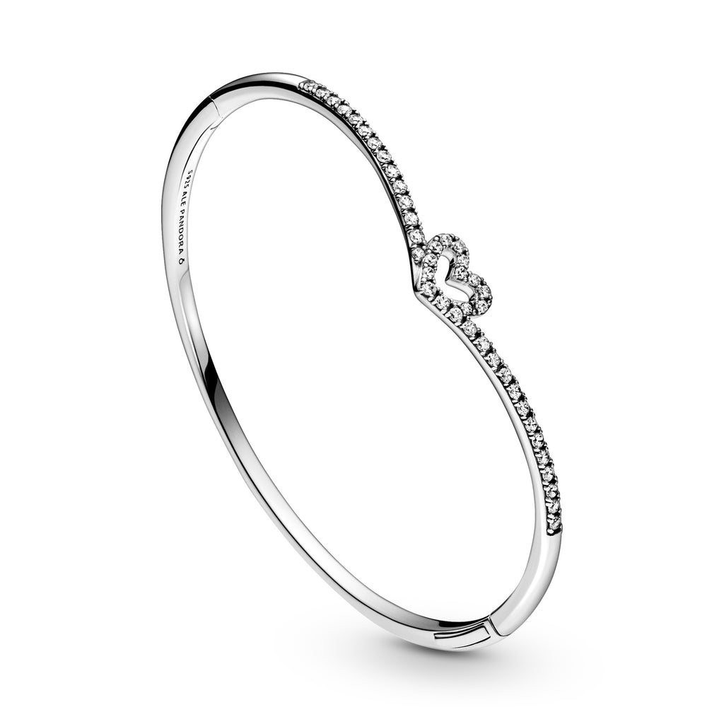 Close up of Pandora Sparkling Wishbone Heart Bangle in sterling silver. The sparkling heart has the Iconic V-shape from the wish collection holding the heart. This openable style features a button for easy on and off.