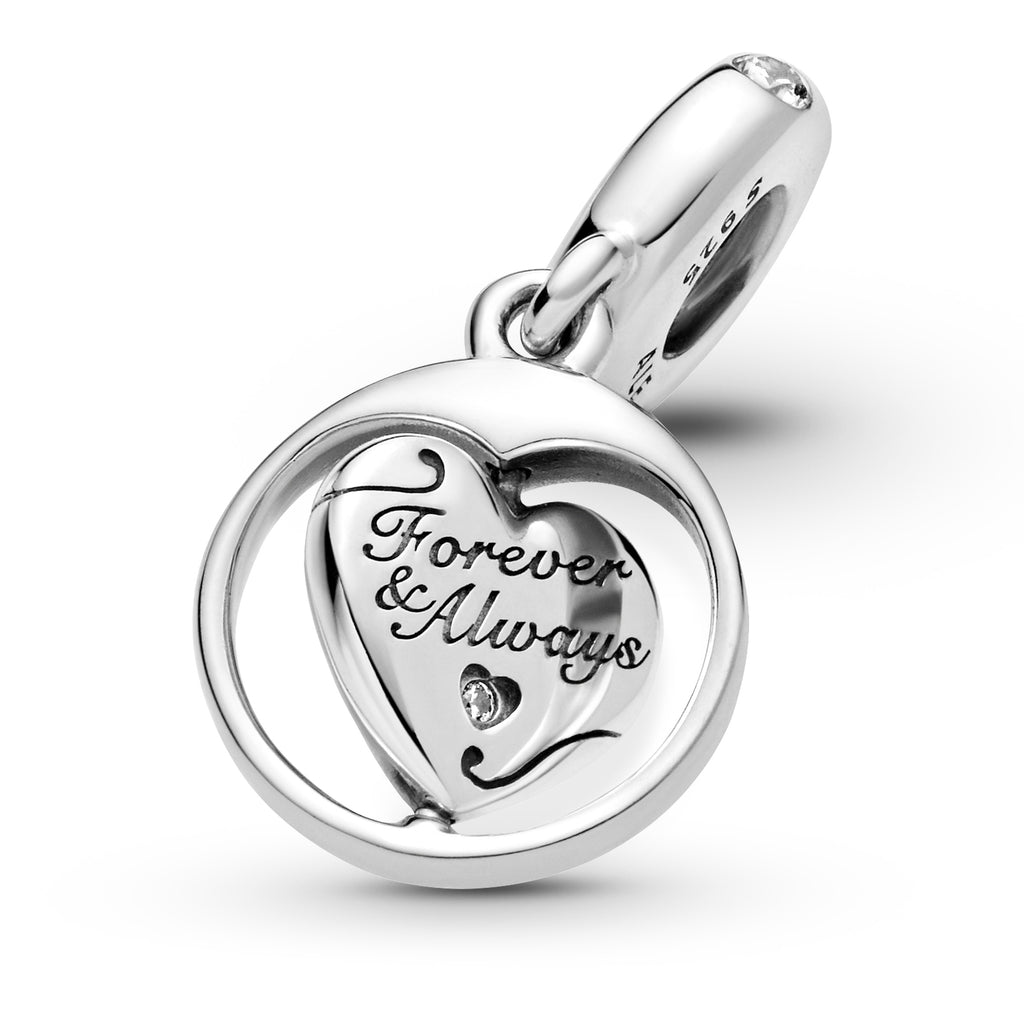 "Partially spinning close up of Pandora Spinning Forever & Always Soulmate Dangle Charm. This sterling silver dangling design has a spinning heart surrounded by a round frame. The heart features the engravings ""Forever & Always"" and ""Soulmate,"" with a sparkling stone inside a cut-out heart on the front and a cut-out star detail on the back."
