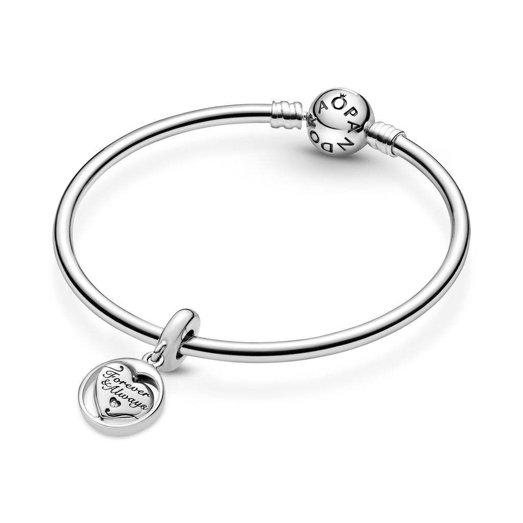 "Pandora Spinning Forever & Always Soulmate Dangle Charm. This sterling silver dangling design has a spinning heart surrounded by a round frame. The heart features the engravings ""Forever & Always"" and ""Soulmate,"" with a sparkling stone inside a cut-out heart on the front and a cut-out star detail on the back. Featured on silver Moments bangle bracelet."