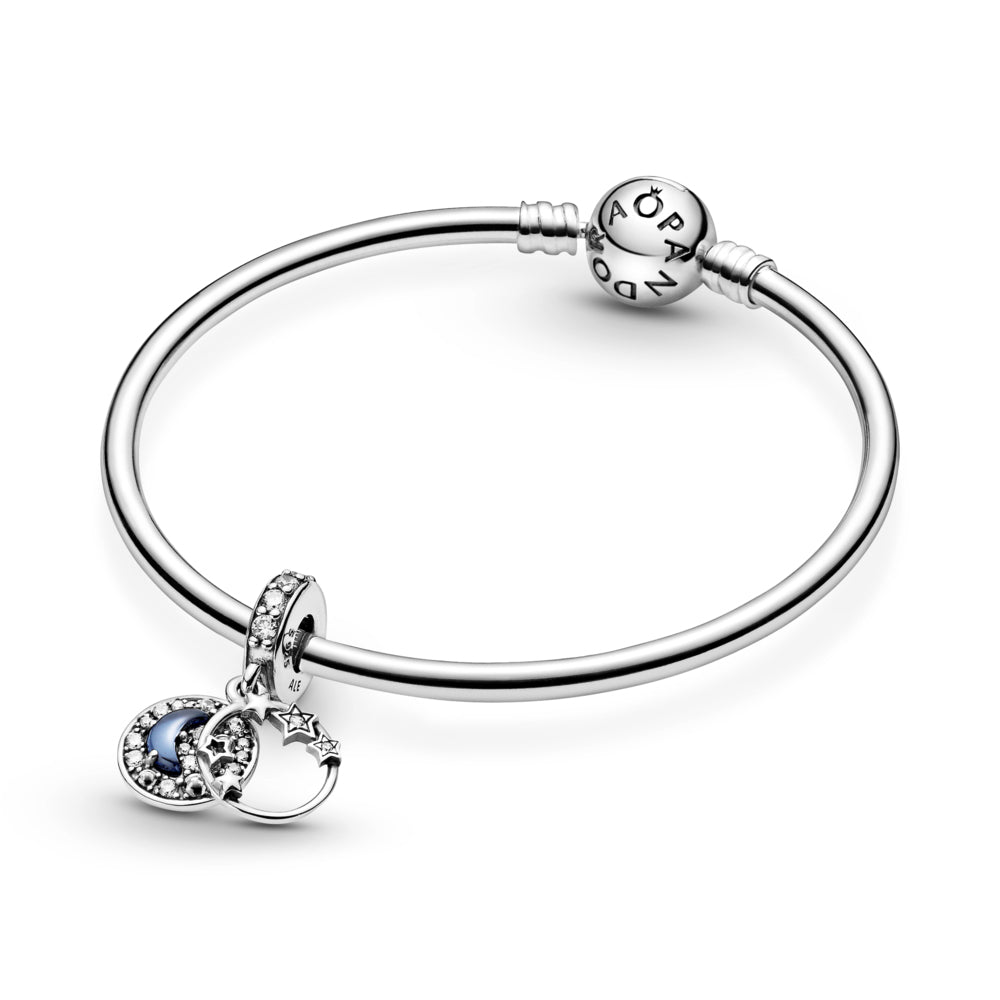 Pandora Blue Night Sky Crescent Moon and Stars Dangle Charm in sterling silver featured on Smooth Sterling Silver Moments Bangle.  The front dangle features an open circle decorated with stars that overlap the frame. The back disc includes a raised blue half-moon-shaped stone surrounded by clear czs. featured on Smooth Sterling Silver Moments Bangle.