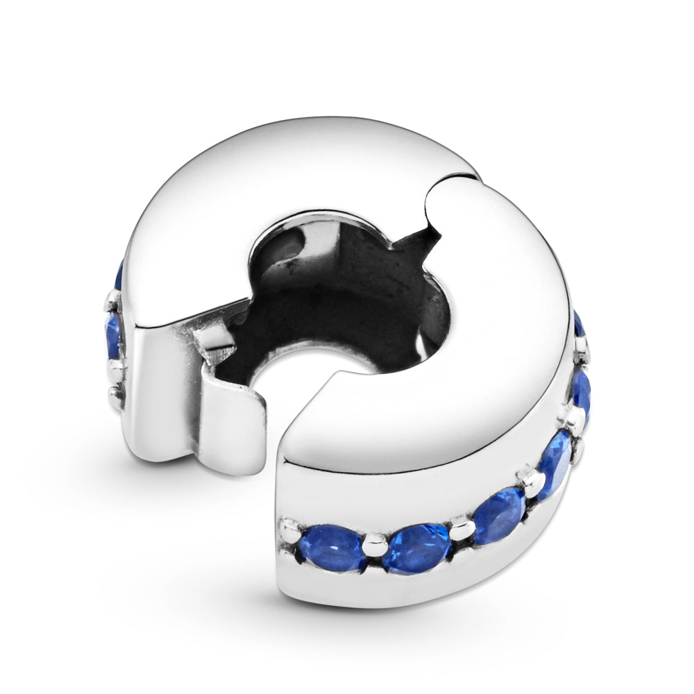 Pandora Blue Sparkle Shining Path Clip Charm. Hand-finished in sterling silver, this classic round design features a centered row of shimmering blue stones is shown on its side and open.