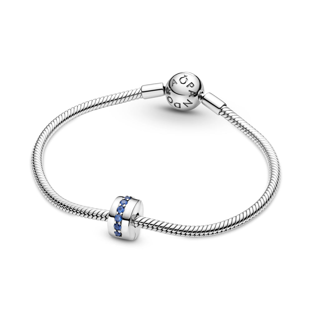 Pandora Blue Sparkle Shining Path Clip Charm featured on Sterling Silver snake chain bracelet. Hand-finished in sterling silver, this classic round design features a centered row of shimmering blue stones.