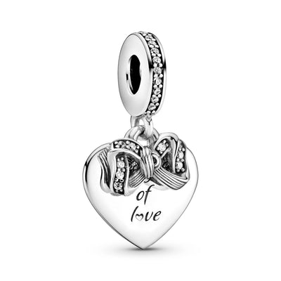 "Pandora Bow & Love Heart Dangle Charm. Hand-finished in sterling silver and features a small dangling bow decorated with clear glittering stones and a flat heart-shaped disc with the engraving ""The gift of love."" A line of sparkling stones featured on the bail"