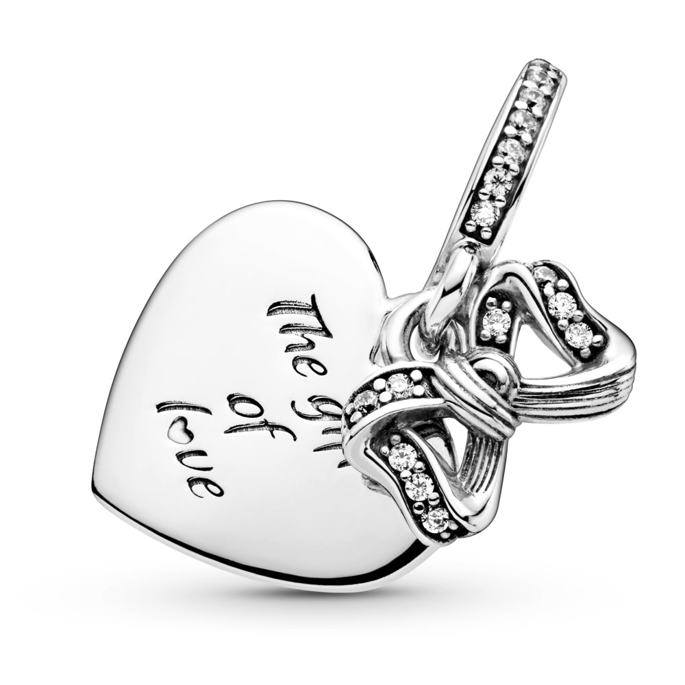 "CLose up of Pandora Bow & Love Heart Dangle Charm. Hand-finished in sterling silver and features a small dangling bow decorated with clear glittering stones and a flat heart-shaped disc with the engraving ""The gift of love."" A line of sparkling stones featured on the bail."