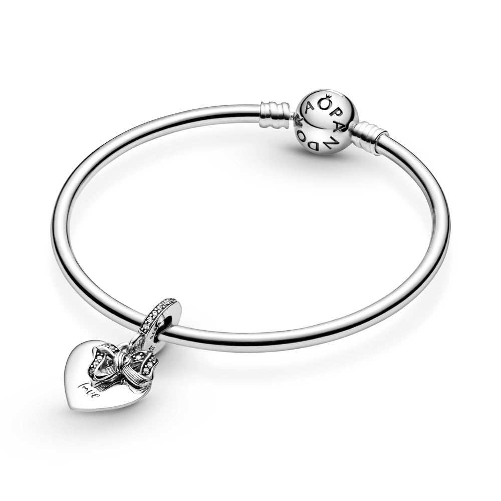 "Pandora Bow & Love Heart Dangle Charm featured on smooth silver moments bangle. Hand-finished in sterling silver and features a small dangling bow decorated with clear glittering stones and a flat heart-shaped disc with the engraving ""The gift of love."" A line of sparkling stones featured on the bail."