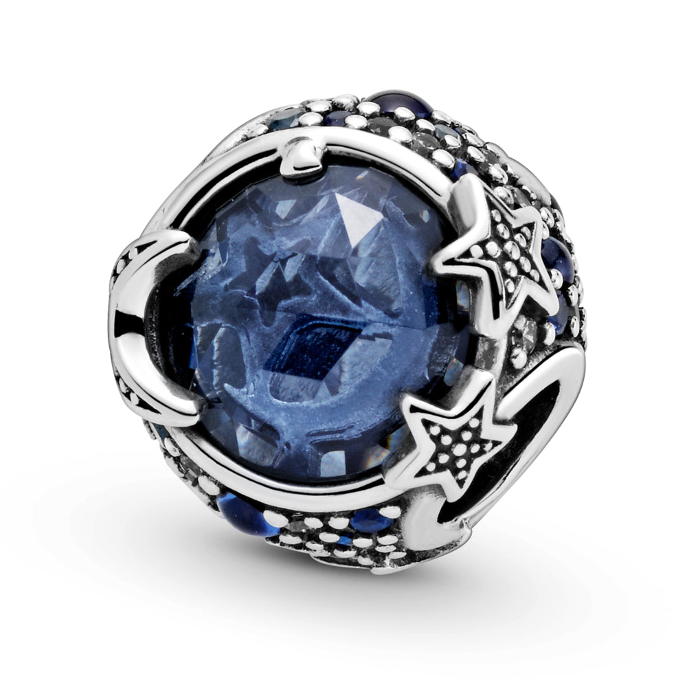Close up of Pandora Celestial Blue Sparkling Stars Charm hand-finished in sterling silver. The rounded design includes a large blue stone in the center that's encircled by blue and clear stones in various sizes. Beaded stars overlap the central stone for added texture.