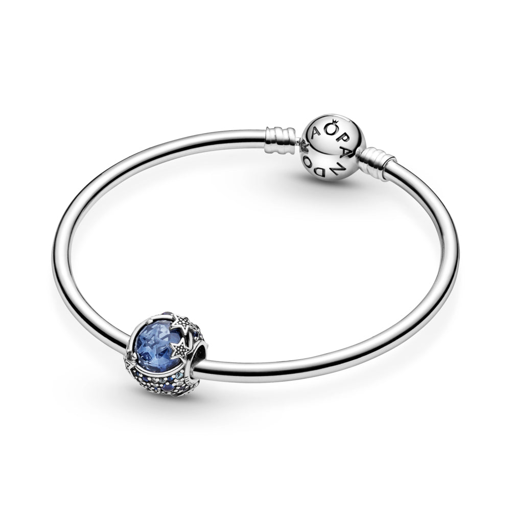 Pandora Celestial Blue Sparkling Stars Charm hand-finished in sterling silver featured on smooth silver moments bangle. The rounded design includes a large blue stone in the center that's encircled by blue and clear stones in various sizes. Beaded stars overlap the central stone for added texture.