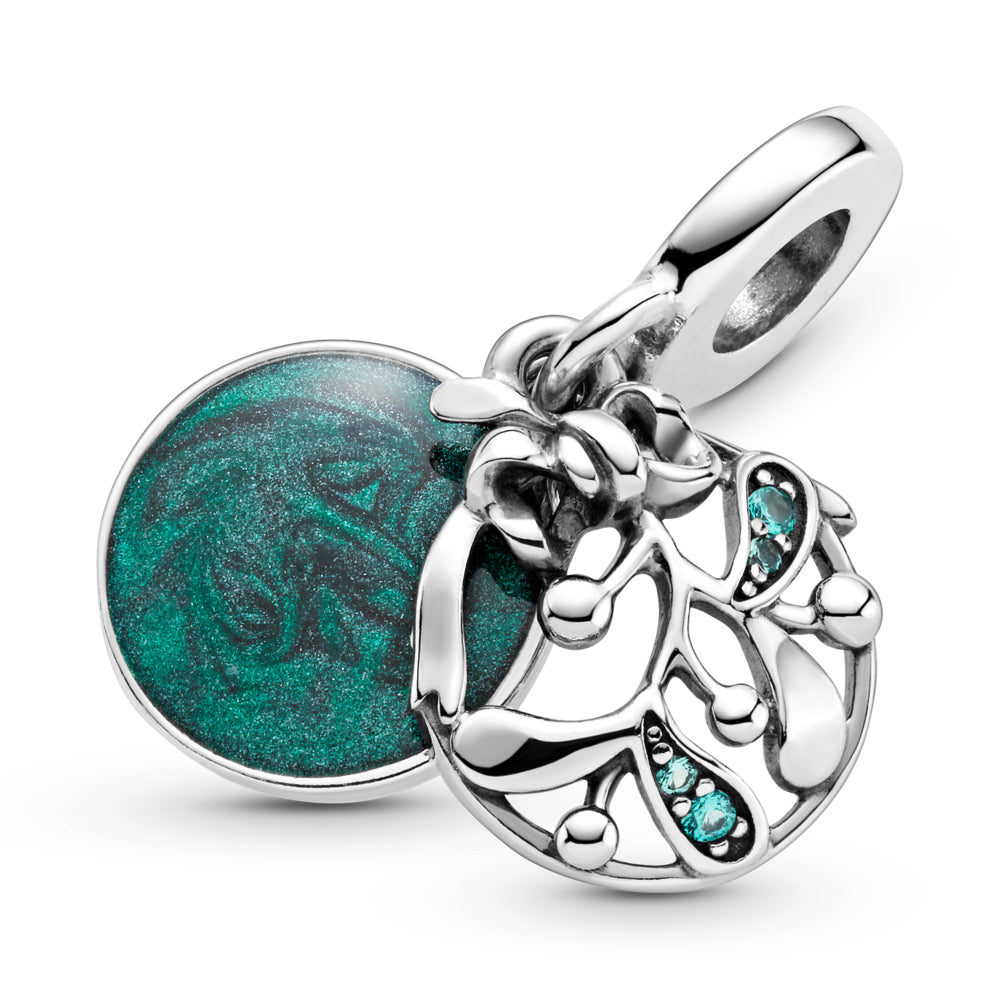 "CLose up of Pandora Christmas Mistletoe Dangle Charm is hand-finished in sterling silver. A front openwork mistletoe dangle is decorated with green stones that hangs at an angle. The back disc features hand-applied shimmering green enamel and the engraving: ""Meet me under the mistletoe."" on the back of the disk. The engraving ""Christmas wishes"" is featured on the side of the bail."